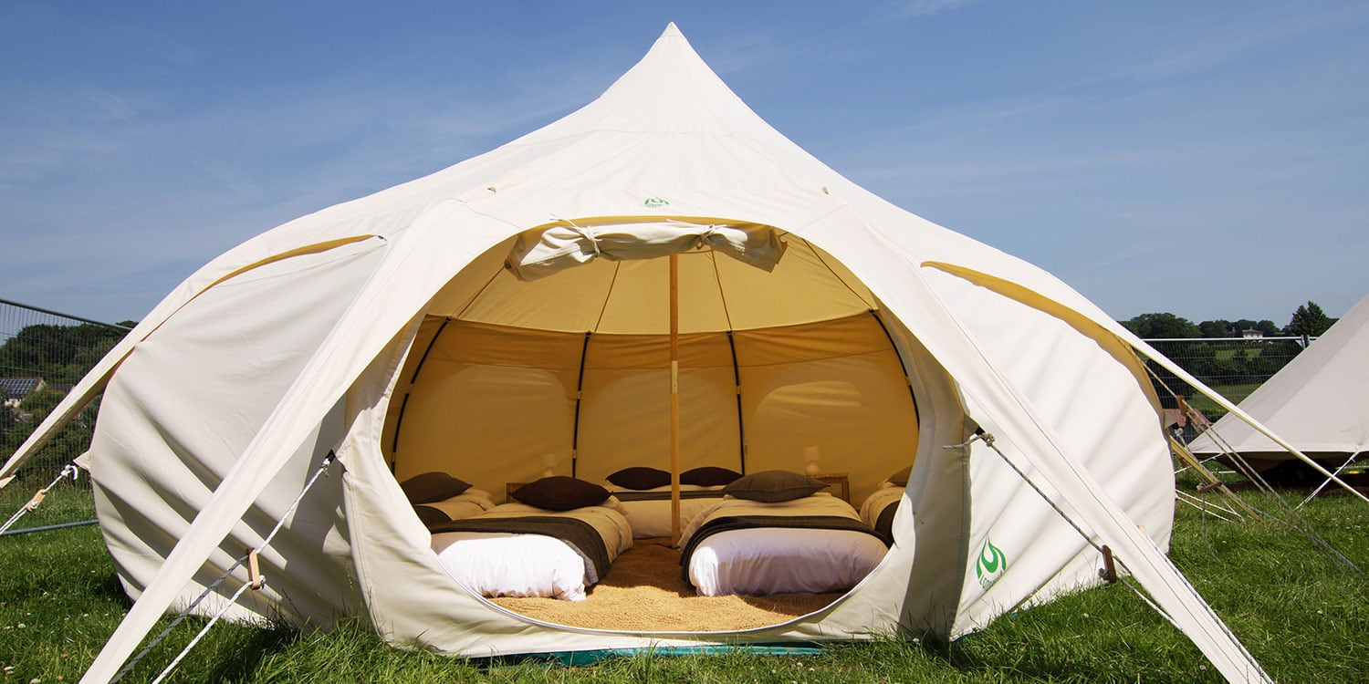 A stunning Lotus Bell tent furnished with four comfy beds and ready for guests to arrive at Glastonbury Festival