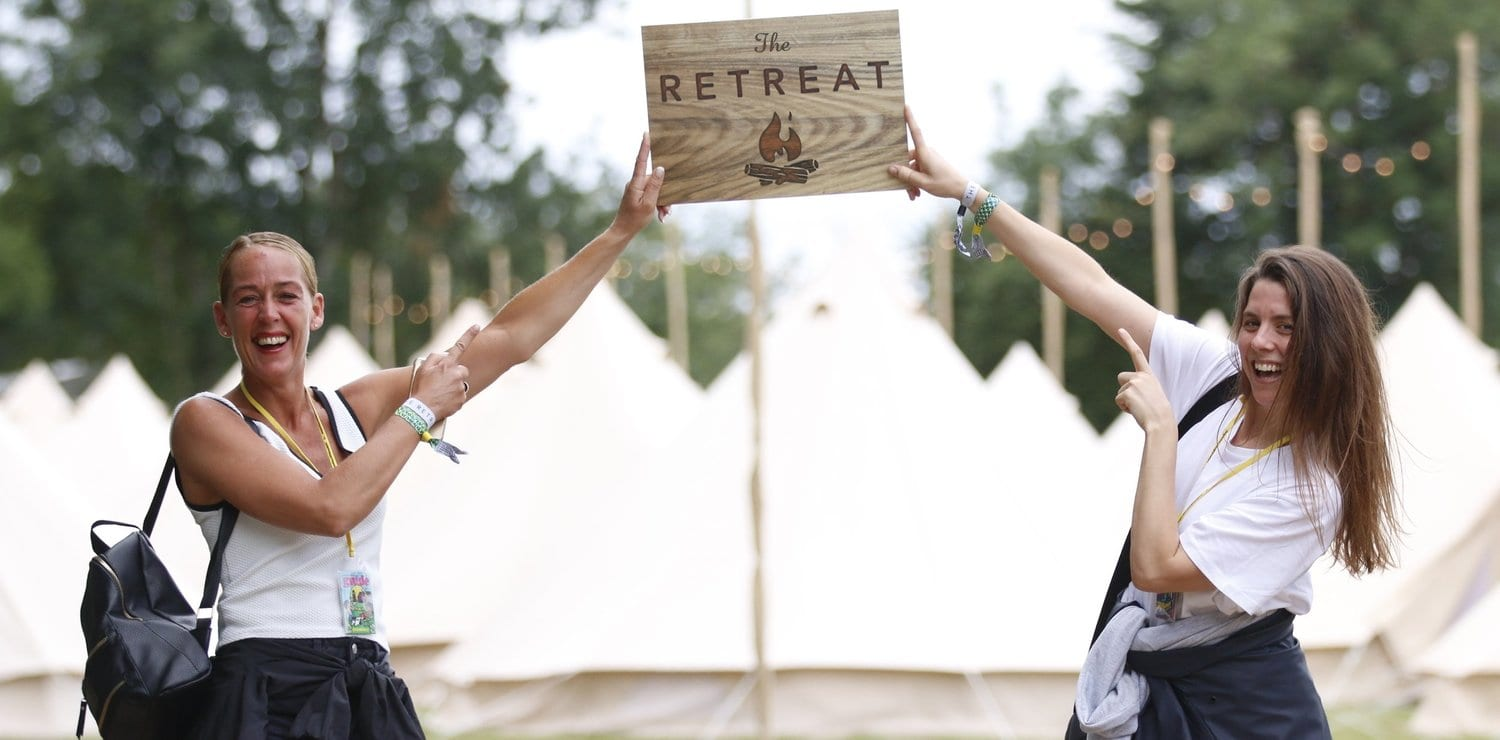 Two happy glampers holding The Retreat logo sign