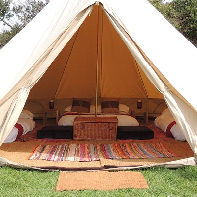 The interior of a furnished Bell Tent at The Retreat, Glastonbury Festival luxury glampsite by Gate Ba