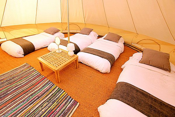 Spacious interior of a furnished 5 meter Classic bell tent at Glastonbury Retreat