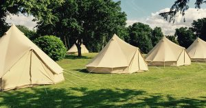 Neat line of beautiful bell tents in a field - Glastonbury glamping
