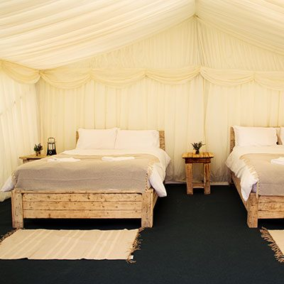 Interior of a luxury frame tent with Ivory lining and real wood double bed