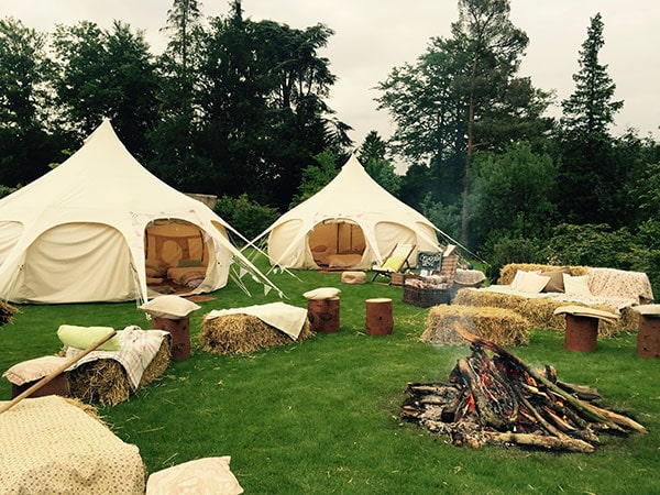 Glamping tents with fire and hay bales in foreground