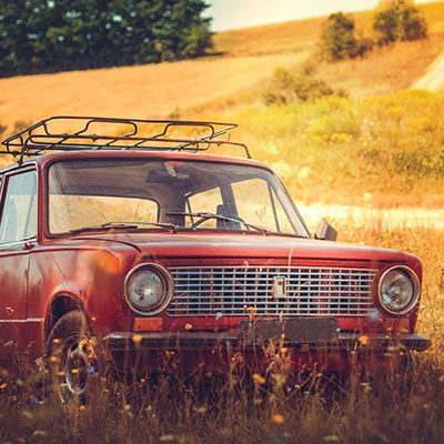 An old red car in a field