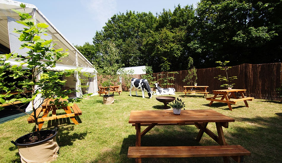 Private secluded sunny bar and garden with life size decorative cow models setting a fun vibe at the Glastonbury glamping site.