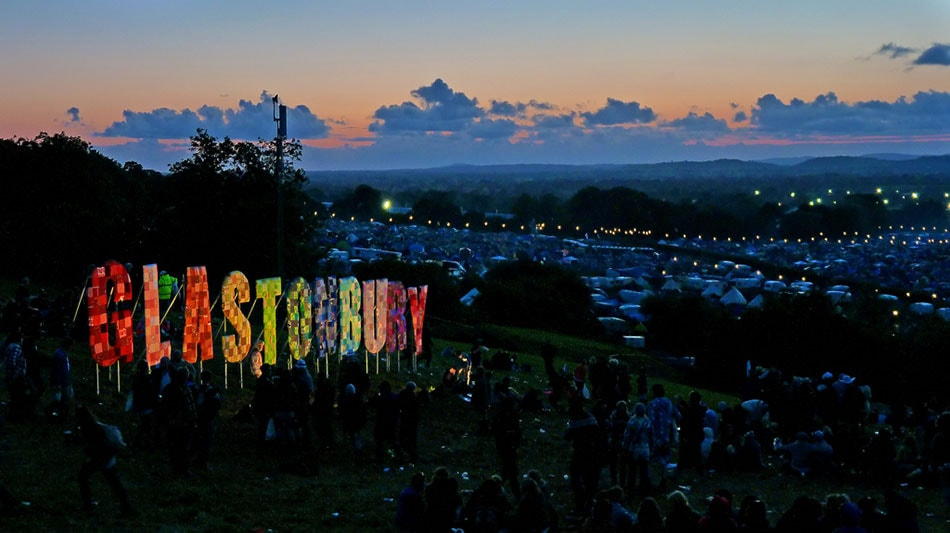 Illuminated Glastonbury sign in a 'Hollywood' style and a twilight view over the Glastonbury Festival site.
