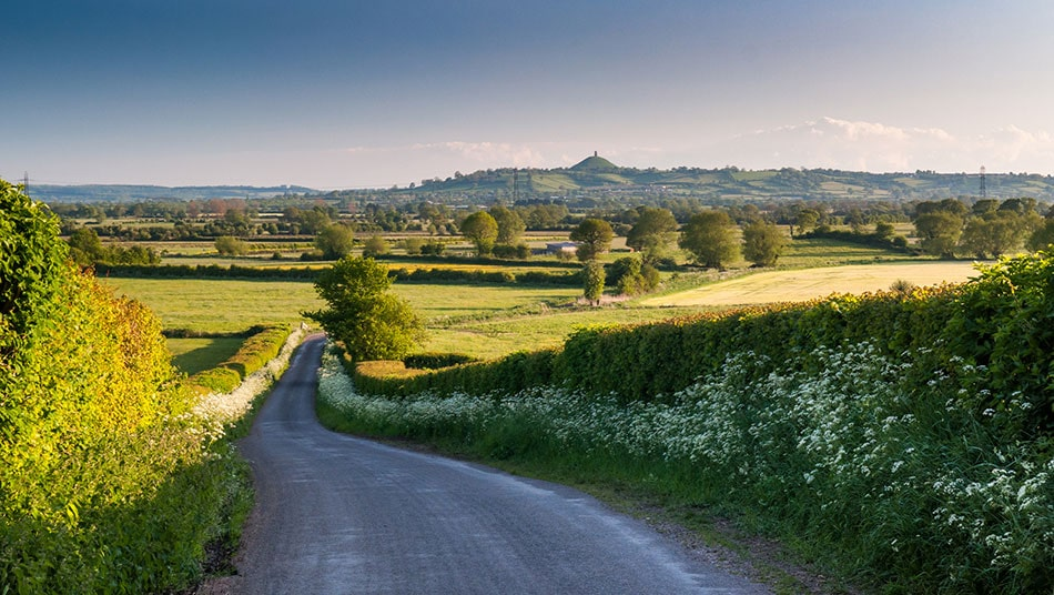 A quiet country lane in the Somerset countryside with Glastonbury Tor in the far distance - the location of The Retreat luxury glamping site